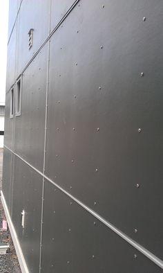 James Hardie panels in dark grey with exposed fastening screws to give a rivet look.