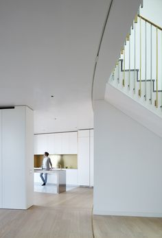 rolling partition rolls against the wall, metal flat railing, white kit., hardwood flooring, white walls
