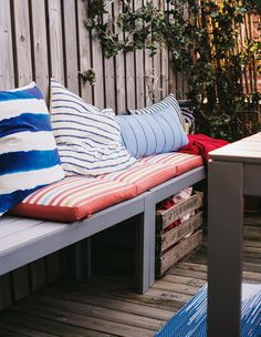A row of wooden benches with cushions, and a box of pillows and blankets underneath.