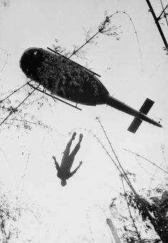 Body of an American paratrooper KIA in jungle near Cambodian border is raised up to an evacuation helicopter in War Zone C, Vietnam, in 1966.