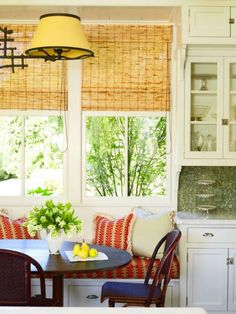 A sunny, kitchen banquette offers lovely views outside. - Traditional Home ® / Photo: Tria Giovan / Design: Jennifer Garrigues