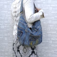 Handmade denim slouchy hobo bag. Hippie, Rock, Boho, Street style, Urban fashion. Made out of a pair of jeans!  Made of recycled denim. I do my bit to save the Planet :) Always prewashed and surely no marks and spots.  Two functional pockets outside. Cotton lining. Zippered closure. Zipped pocket inside.  Machine washable.  The bag is medium fatty shape. But youll fit loads inside! The model on photo is XS-S.  Measurements are going to be tricky due to shape, but lets try. The zipper is 16…