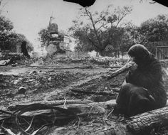 Russian peasant woman weeping near smoldering ruins of her home which was razed by retreating German soldiers