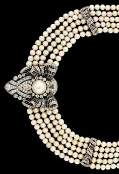 An Art Deco natural pearl and diamond necklace with clip brooch. Of collar design, composed of four and then five rows of graduated pearls, interspersed with diamond-set openwork bow design spacer panels, suspending a central diamond-set shield shaped pendant/clip brooch, with a central natural pearl highlight, to an old-cut diamond cluster surround with adjacent fancy and marquise-cut diamond accents, circa 1930.