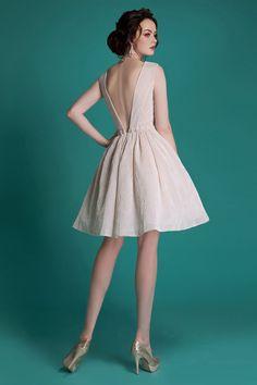 Кремовое свадебное платье пышного кроя с глубоким V-образным декольте на спинке и юбкой до колена.