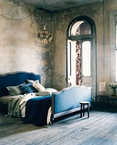 i love the weathered walls and floor and who doesn't want big glass doors streaming with light in their bedroom?