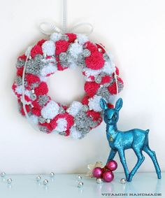 Holiday PomPom Wreath Tutorial: Attach handmade pompoms in red, white, and grey to a styrofoam wreath, and add scattered shiny beads for a small pop.