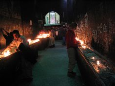 Crypt inside the main church in Copacabana, Bolivia. People use the wax from the candles to draw pictures of the things they'd like blessed on the walls.