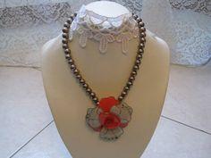 Collana con perle di colore viola metallico e fiore centrale in resina di colore rosso e grigio e con piccoli strass. Chiusura argentata.