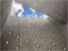 Un bloc monolithique perforé de pavés ronds abrite une crèche parisienne.