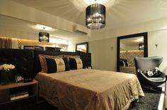 Este quarto, de 14,4 m², foi projetado pela arquiteta Camila Moraes. O destaque do ambiente fica por conta da cabeceira da cama, que é estofada e revestida com um tecido sintético semelhante ao couro natural e preto.