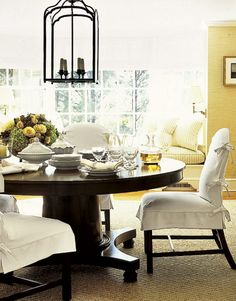 love the window seat tucked behind the dining room table.  love the slipcovered chairs