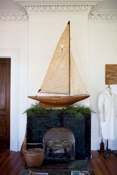 Perched atop the mantel, an antique sailboat anchors the living room. (Photo Credit: Patricia Lyons)