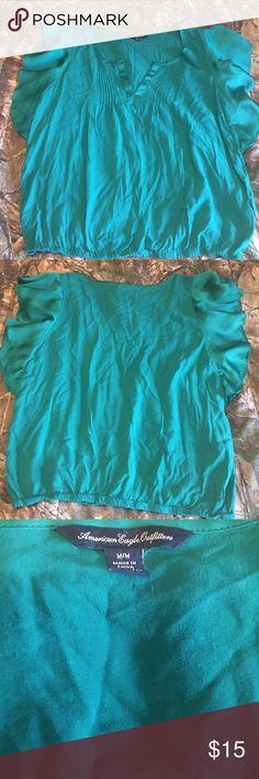 American Eagle Green Sleeveless Blouse American Eagle green sleeveless blouse size medium. Shirt is sleeveless but has nice ruffles/flowey material at sleeves to add a very feminine touch. Only flaw is small hole (see picture 3) where for some reason the price tag was attached. Smoke free home. American Eagle Outfitters Tops Blouses
