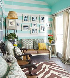 The couple hired a contractor to turn an underused back patio into a more useful enclosed space. They painted what was once exterior siding in stripes of white and robin's-egg blue, then cozied up the space with plump pillows, greenery, and family photos. Home Improvement Contractors, Diy Home Improvement, Decorating On A Budget, Porch Decorating, Sky Blue Paint, Diy Porch, Porch Ideas, Small Front Porches, Starter Home
