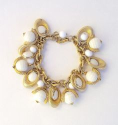 Vintage Bracelet of White Dangles Charms are Framed with Gold Tone