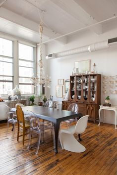 "Sneak Peek: An Eclectic Philadelphia Loft. ""Bentwood dining table is from DWR. I painted the chandelier a high gloss white for an event I worked on. The chairs around the table are a mix that I have collected over the years – Ghost chairs, Pantone chairs and vintage flea market finds."" #sneakpeek"