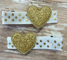 Adorable petite gold glittery hearts sitting on top of ribbon lined double prong alligator clips. These clips measure 1 3/4and have been lined in high quality grosgrain ribbon. All ends have been heat sealed to prevent fraying. A no-slip grip has been added to help hold the finest