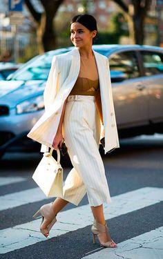 Miroslava Duma atravessa a rua na faixa de pedestres usando blusa marrom com transparência, conjunto de blazer com risca de giz off white e calça pantalona cropped de risca de giz off white, sandália nude e bolsa kelly hermés