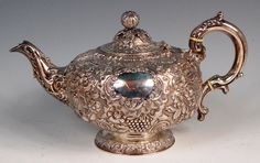 A George IV Irish silver teapot, of bullet shape, having a hinged dome cover, the whole profusely embossed with C-scrolls, scroll leaves and flowers, having opposing vacant cartouches and raised on a footed base, the handle with ivory insulators, 37.9oz, maker William Nelson, Dublin 1823, h.18.5cm