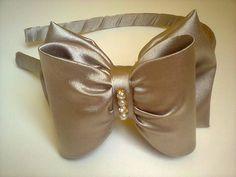 Tiara infantil laço, confeccionada em cetim cor dourada com acabamento em strass.