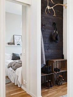 drewniane skrzynki w roli półek na buty we wnęce zczarną boazerią z desek  małego przedpokoju  - Lovingit.pl