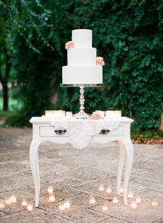 gorgeous white cake with lace doilies and votive candles | love the coral flowers| photo by lemma keech
