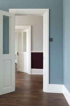 Foreground walls in Farrow & Ball's Oval Room Blue. Hallway walls in Brinjal and Cornforth White Modern Emulsion. Woodwork in Wimborne White. bath Oval room Blue, panelling pale putty colour, walls - cornforth white OR purbeck stone. Oval Room Blue, Blue Rooms, Baseboard Styles, Baseboard Trim, Baseboard Ideas, Wimborne White, Cornforth White Living Room, Hallway Colours, Hallway Colour Schemes