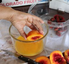 freezing peaches == cut in half, dip in orange juice, place on flat tray, freeze till firm - place in ziplock bag, date bag == to use, run frozen peach under water to slip the skin off then use in smoothies, pies, etc.