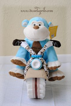 """Materials: 34 diapers Pampers Swaddlers Size 1 (17 for each tire), 8"""" cake pan, 2 rubber bands, 2 receiving blankets, 2 bibs, 1 chain link toy, a pair of socks or mittens, a baby bottle, 1 washcloth, scissors, pins, a stuffed animal, and decorative ribbon."""