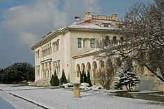The Royal compound (Serbian: Краљевски комплекс) is located in Dedinje, a prestigious area of Belgrade, Serbia. It consists of two palaces: Kraljevski dvor (Royal Palace) and Beli dvor (White Palace).  Kraljevski dvor (Royal Palace)    It is a grand stucco villa in the Serbian-Byzantine style by architect Živojin Nikolić and assisted by Russian immigrant architects Nikolai Krasnov and Victor Lukomsky, was built from 1924 to 1929 as an ideal home for King Alexander I and Queen Maria.