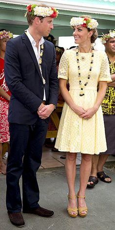 """FLOWERS IN HER HAIR  In another enviable yellow number – plus her Stuart Weitzman """"Minx"""" wedges and accessories courtesy of the Tuvalu locals – the Duchess is all smiles next to her equally well-accessorized husband."""