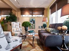 This small sitting room is full of windows with woven wood blinds, featuring a midcentury blue couch, two upholstered chairs, and a metal coffee table with Queen Anne legs. Eclectic Design, Interior Design, Mid Century Modern Couch, Small Sitting Rooms, Woven Shades, Patterned Chair, Blue Couches, Custom Curtains, Colorful Furniture