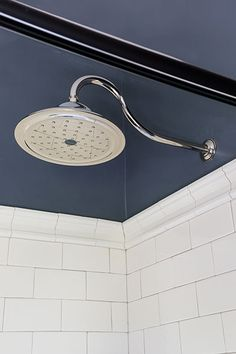 A gooseneck rain showerhead by Delta in nickel finish is in keeping with classic Victorian-style fixtures and matches the pedestal sink's new faucet.