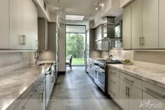 creamy hued galley kitchen with marble & stainless