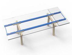 """8 de Mayo de 2014. Alain Gilles diseña la mesa """"Tracks"""" una mesa rectangular extensible de cristal. Hasta aquí no hay nada de novedoso. Lo que la hace diferente es que las patas están ligeramente separadas a modo de caballetes con una cruceta que soporta un bastidor metálico que puede ser de distintos colores. Sobre este bastidor está una tapa de cristal transparente para que se pueda contemplar cada uno de estos detalles de la mesa."""
