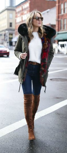 olive green parka with multi-color fur lining, brown braid belt, brown over the knee flat boots, chunky knit ivory sweater, cat eye tortoise shell sunglasses