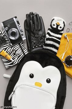 An unstructured backpack featuring a penguin design, zip-around top, front zippered pocket, adjustable shoulder straps, an interior zippered pocket, and two interior slit pockets.