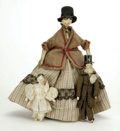 """England, ca. 1830, including peg wooden lady in period wool and cotton clothing and 2 small peg wooden male and female dolls with early handmade clothing, all dolls have painted and molded features, painted black hair and wooden jointed bodies  Size: largest 7"""" t."""