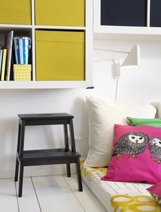 Monochrome Ikea teenagers bedroom with bright yellow and pink storage and cushions