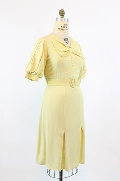 Stunning late 30s rayon frock! Done in a soft sunny yellow rayon crepe. Bodice is adorned with a large bow that sits at neckline. Small heart