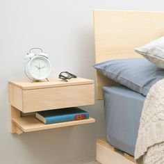 Floating bedside table. Solid natural beech, matt finish. One shelf and one drawer for plenty of storage in smaller bedrooms where space is limited. Also works well in a hallway. Really easy to fit to the wall, 2 keyhole slots in the back of the unit will hook onto two screws in the wall. Fits nice and snug to the wall.  Measurements: L30cm x W20cm x H24cm  IN STOCK NOW