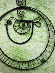 Ptáček v kolečku se zelenou perličkou Ptáček je vyroben z černého drátu a dozdoben korálky.Průměrkolečka je cca 12cm. Ptáček slouží jako dekorace.Drátek je ošetřen proti korozi. Cena za kus.