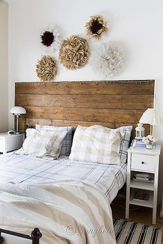 Bedroom decorations in neutral colors with a reclaimed wood headboard and a collection of homemade African feather Juju hats/wreaths. via http://www.songbirdblog.com