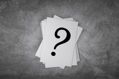 paper card on a concrete table with question mark sign with free