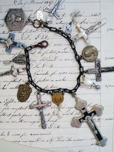 Rosary Cross Repurposed Bracelet with St. Teresa  This one has 7 vintage crucifixes including silver, mother of pearl and wood with silver. There are also 4 vintage connectors from vintage rosaries that join the strand to the portion with the cross. I have dangled 3 different mother-of-pearl vintage rosary beads and a metal bead from a soldier's rosary to the bottoms of those connectors, too!...