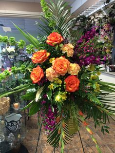 High & Magic roses, carnations,purple stock,yellow alstroemeria,boronia,orange gladiolus,& unique greenery designed by Cyndy Smith