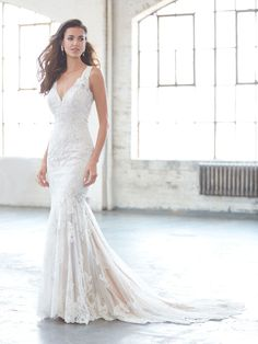 Sheer netting, topped with lace appliques, is the backdrop of this ultra-flattering sheath.   MJ305  http://www.charlottesweddings.com/for-the-bride/request-appointmen/