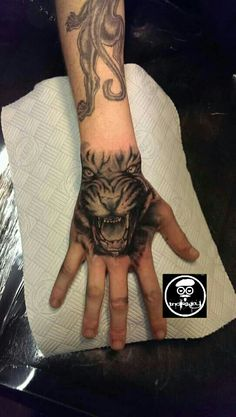 Realistic Black and gray tiger on hand tattoo