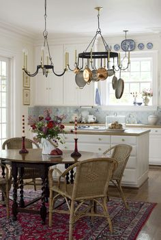 Matching custom-made chandeliers by Ball & Ball Antique Hardware--one over the breakfast table and another one complete with a pot rack--provide a focal point.